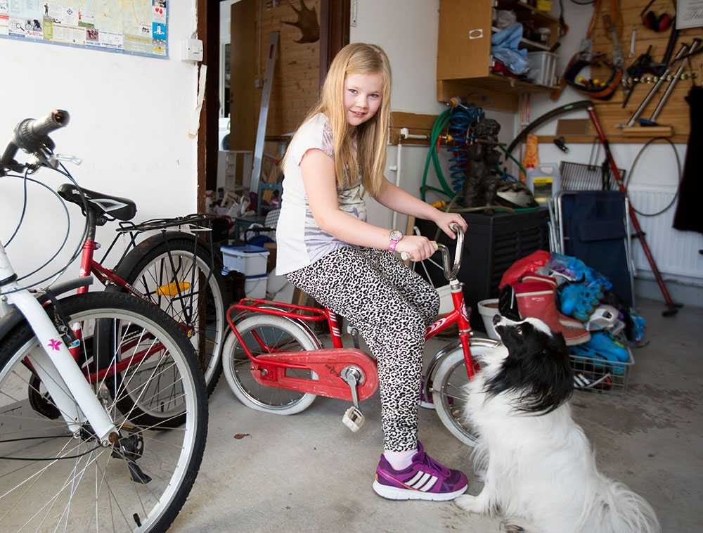 Cornelia provsitter en cykel hon vuxit ifrån för länge sedan.