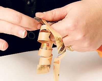 4 Ta spillbiten och skär till några långa remsor och klipp även ut en fyrkant (som blir etikett) med en mönstersax. Krulla pappersremsan med saxen (så som du gör med presentsnöre).