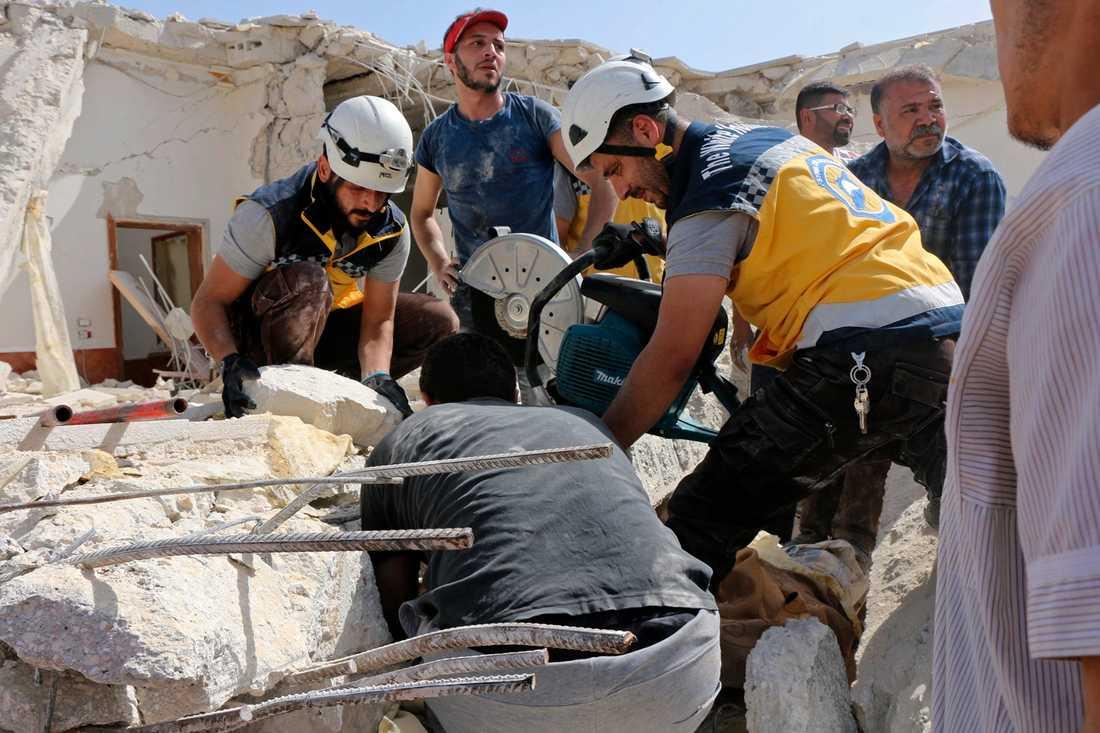 En bild som tagits av civilförsvaret Vita hjälmarna, och vars äkthet har verifierats av nyhetsbyrån AP, visar räddningsarbetare som på i torsdags letade efter människor i rasmassor efter ett flyganfall mot staden Maarit al-Numan i södra Idlibprovinsen.
