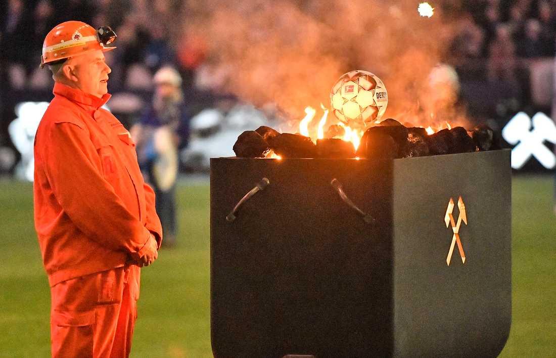 En gruvarbetare står givakt vid en schaktvagn med en fotboll på under veckans match mellan Schalke och Bayer Leverkusen i Gelsenkirchen, Tyskland.