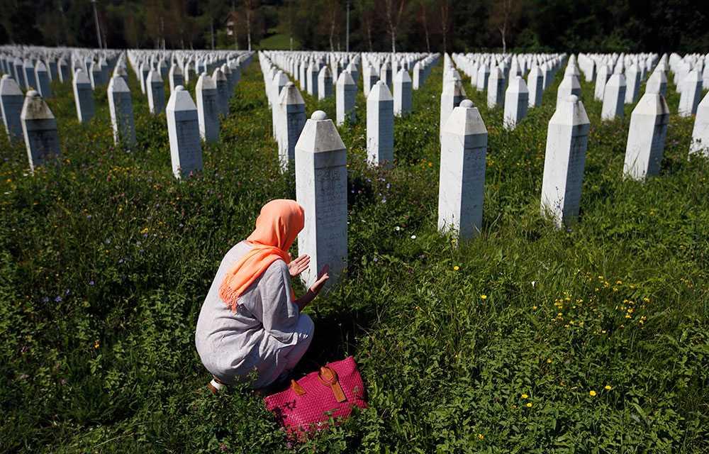 En bosniakisk kvinna knäböjer vid gravplatsen på minnescentret Potocari i Srebrenica.