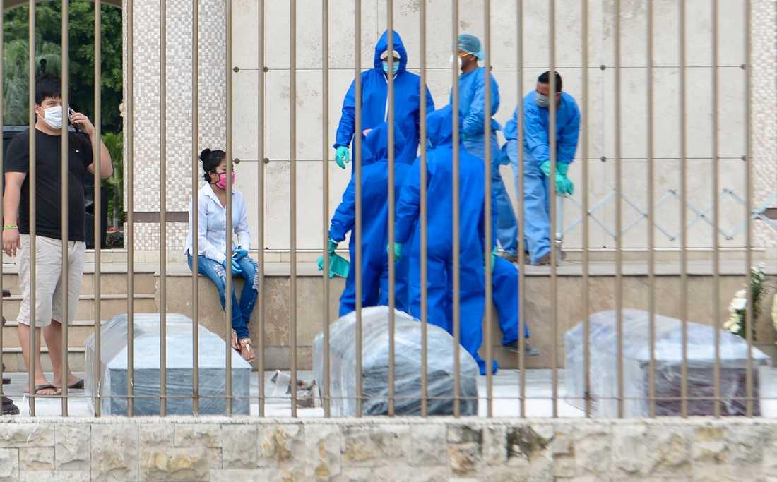 Plastinlindade kistor bärs iväg av människor i skyddsmundering i Guayaquil.