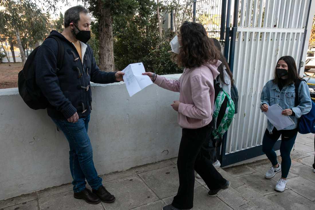 Gymnasieelever visar upp sitt testresultat på väg in i skolan i Atens förorter på måndagen.