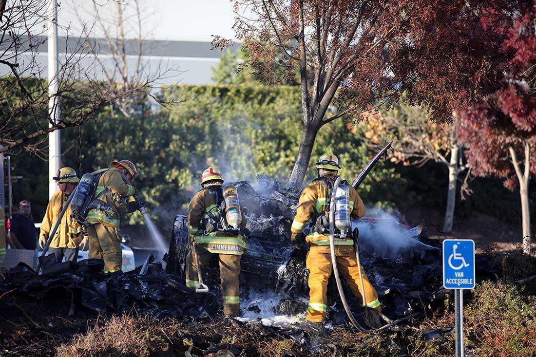Brandmännen släcker resterna av superbilen.