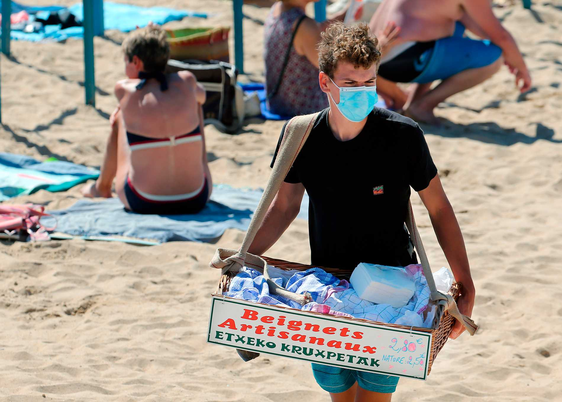 Nu slipper snart fransmännen bära munskydd utomhus – vilket säkert glädjer den här försäljaren av munkar på en strand i Saint-Jean-de-Luz. Arkivbild.