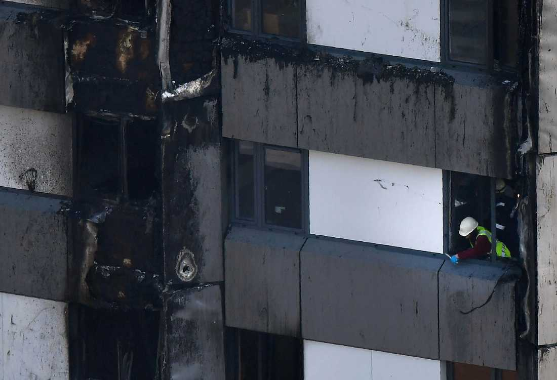 Räddningspersonal jobbar sig uppåt i den utbrända fastigheten.