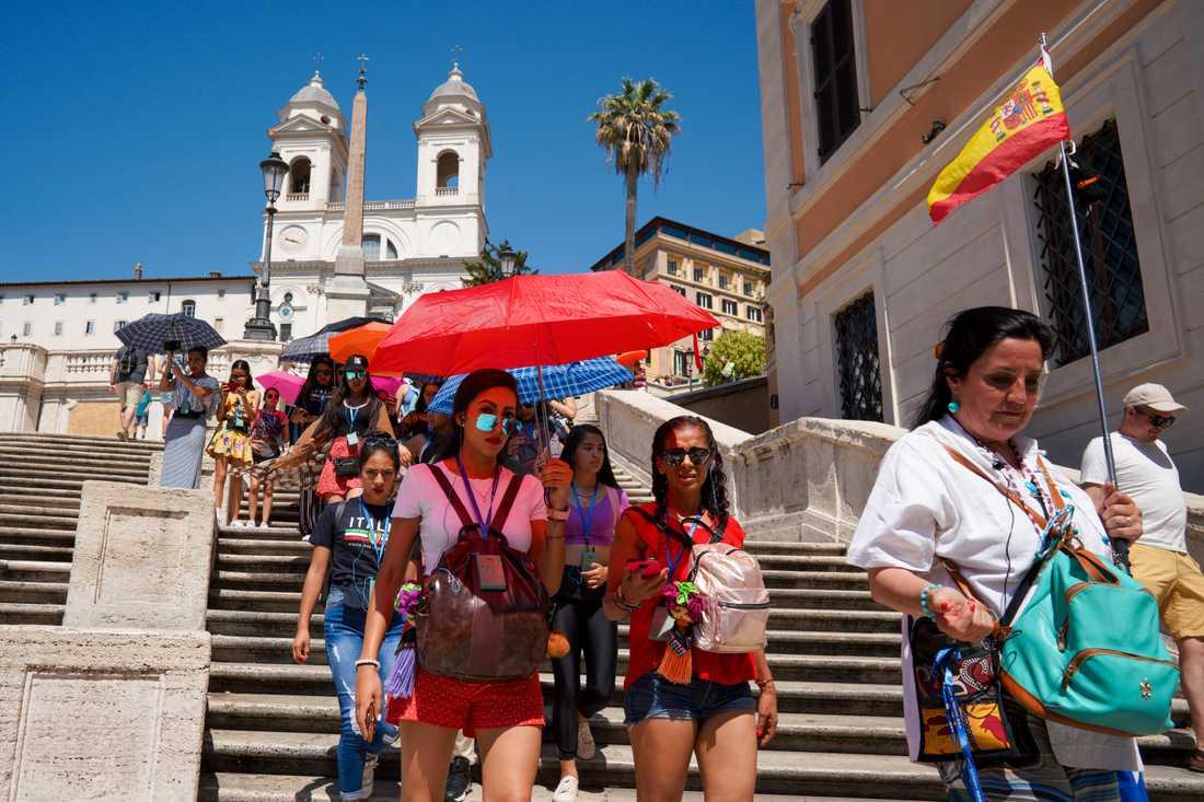 Turister skuggar sig med paraplyer när de går nerför Spanska trappan i Rom på tisdagen.