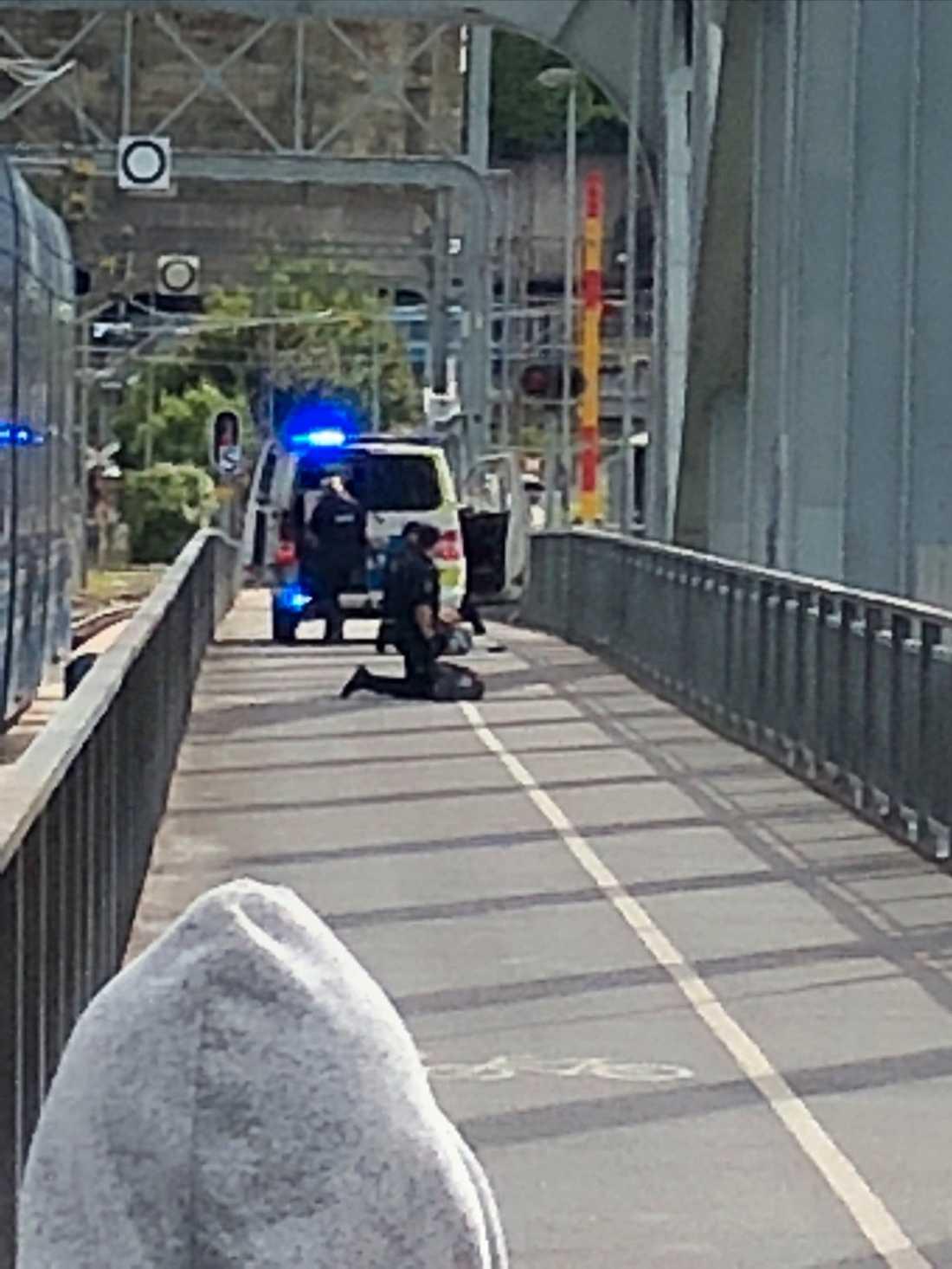 En person grips på en gångbro efter skjutningen.