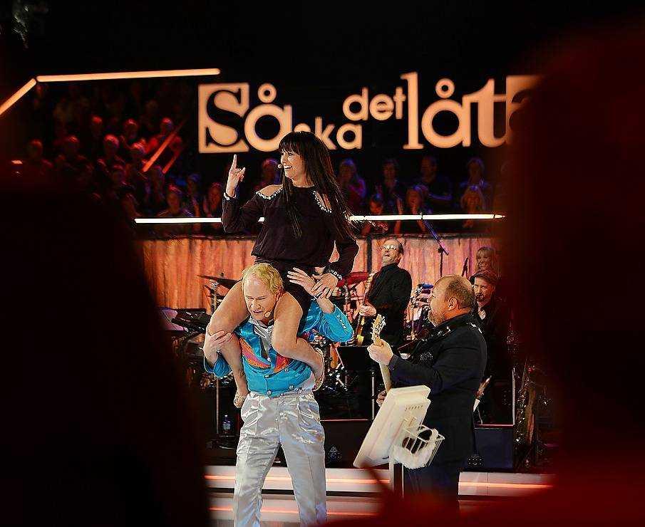 """17.38 Rock'n'rollen tågar in i byggnaden, förklädd till ett gitarrsolo signerat Kalle Moraues. Samtidigt får Erica Sjöström feeling och hoppar upp på Rolands axlar. 18.00. Paus. En kvinna i publiken skriker åt studiomannen att """"göra lite moves"""". Efter några om och men bjuder han till slut på höftskak. Genast flyger mobiltelefonerna upp i publiken och stunden förevigas digitalt."""