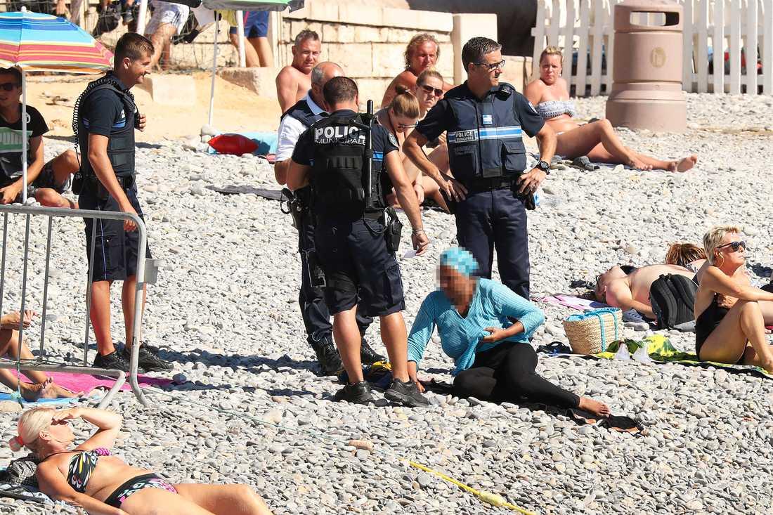 Poliserna hotade kvinnan med pepparsprej och bad henne ta av sig huvudduken.