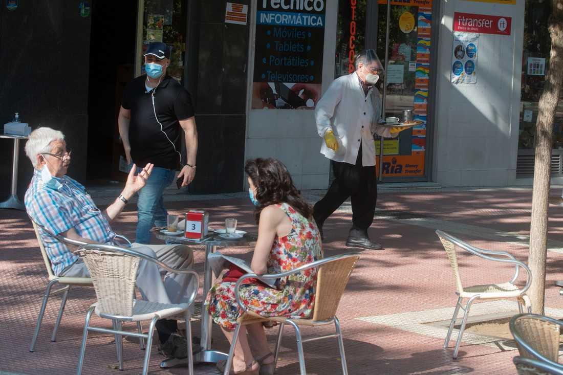 En kypare i munskydd och handskar serverar gästerna i Madrid på måndagen, när uteserveringar i huvudstaden och i Barcelona tilläts öppna igen.