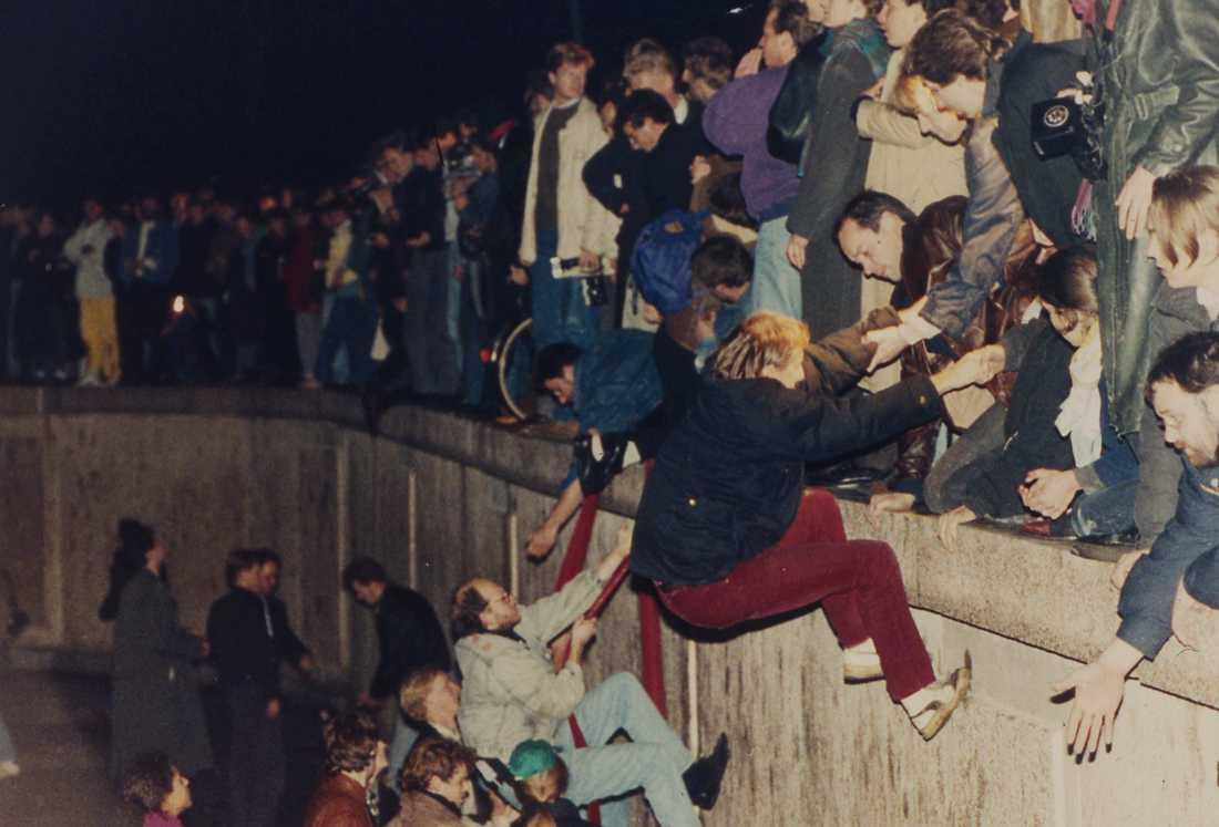 Östberlinare får hjälp av Västberlinare att klättra över muren den 10 november 1989.