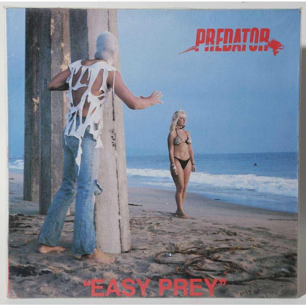Predator - Easy Prey Orkestern Predator försökte sig på att sälja skivor med en maskerad man (med en jättekonstig t-shirt) lurpassande på en inte ont anande kvinna på strandpromenad.