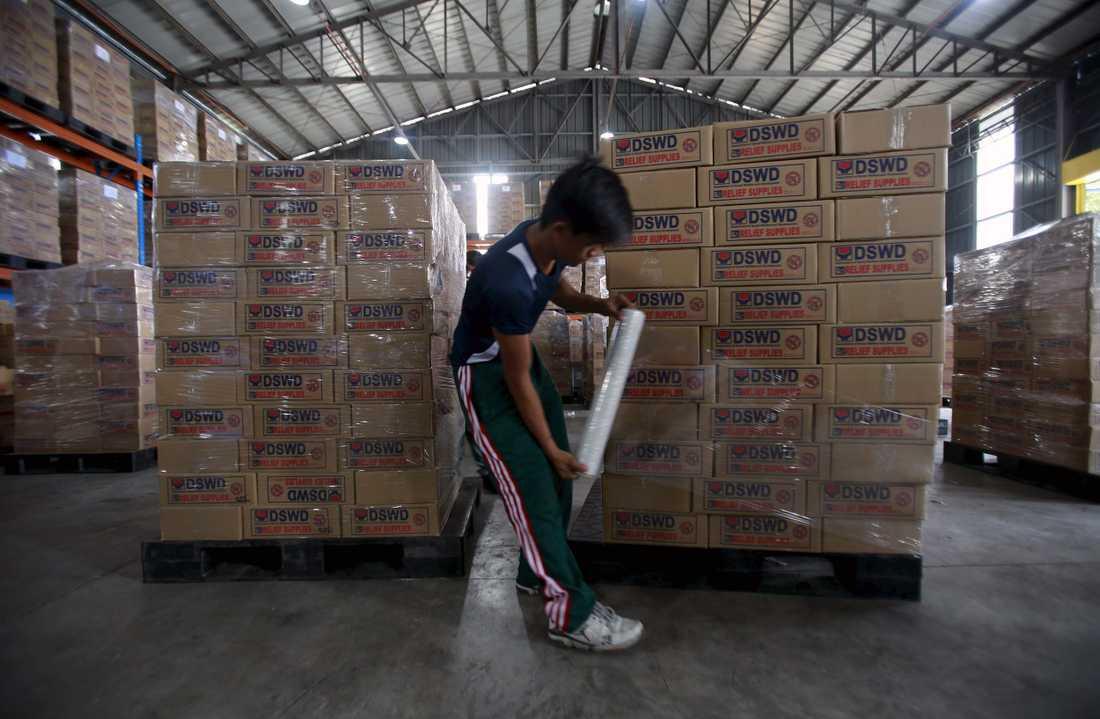 En man förbereder förnödenheter som ska flygas ut i landet.