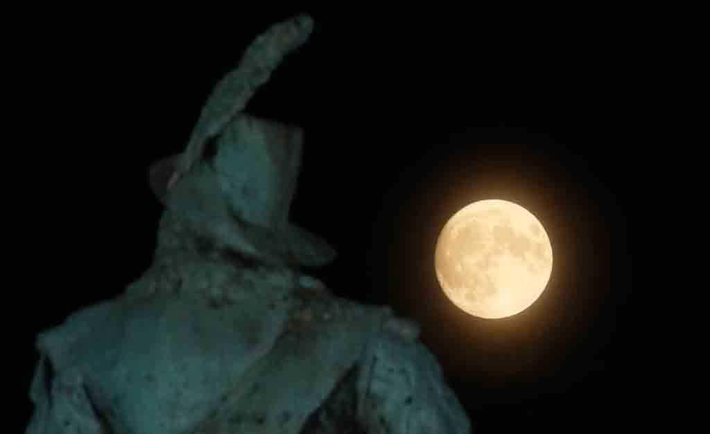 Supermånen går upp bakom statyn av Karl X Gustav på Stortorget i Malmö på söndagskvällen.