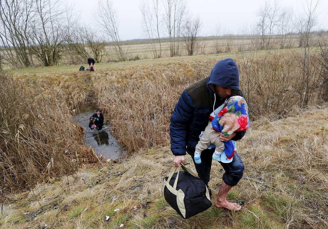 En man bär på sitt barn när han illegalt tar sig in i Ungern från Serbien i februari i år.