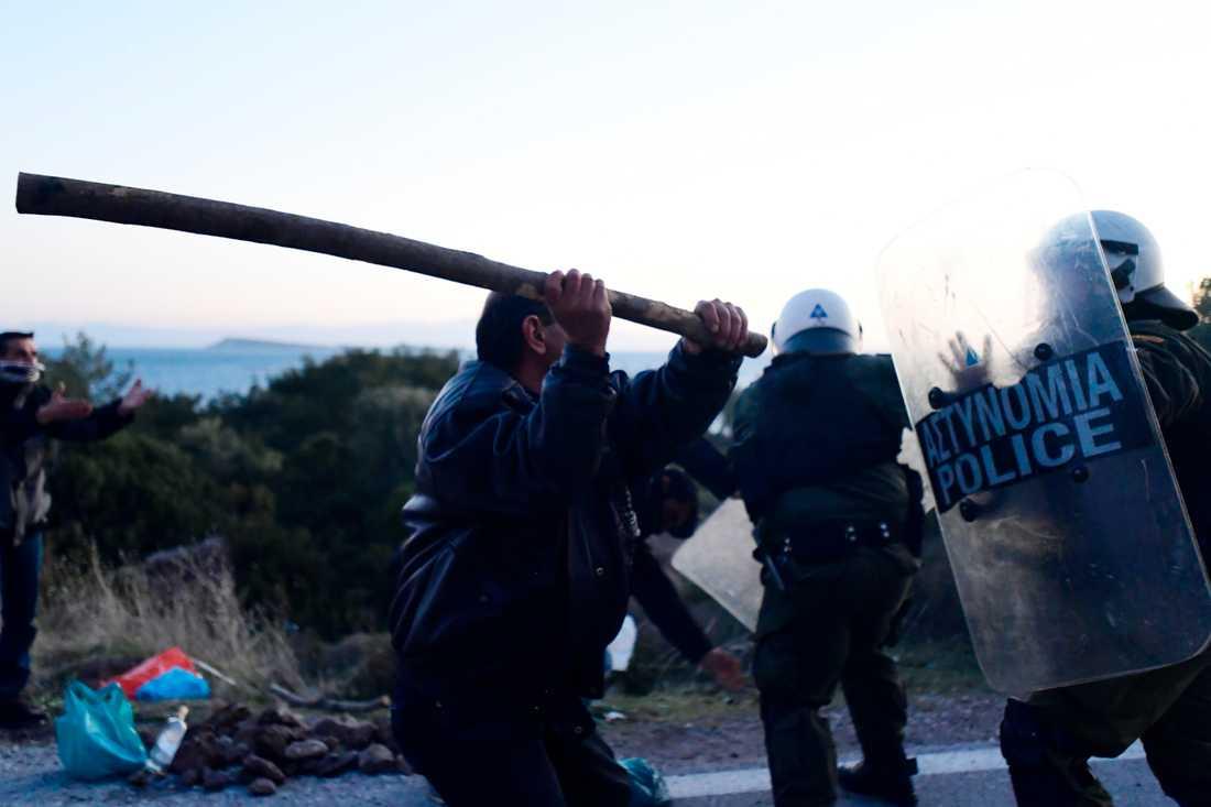 En lokalinvånare går till attack mot kravallpolis.