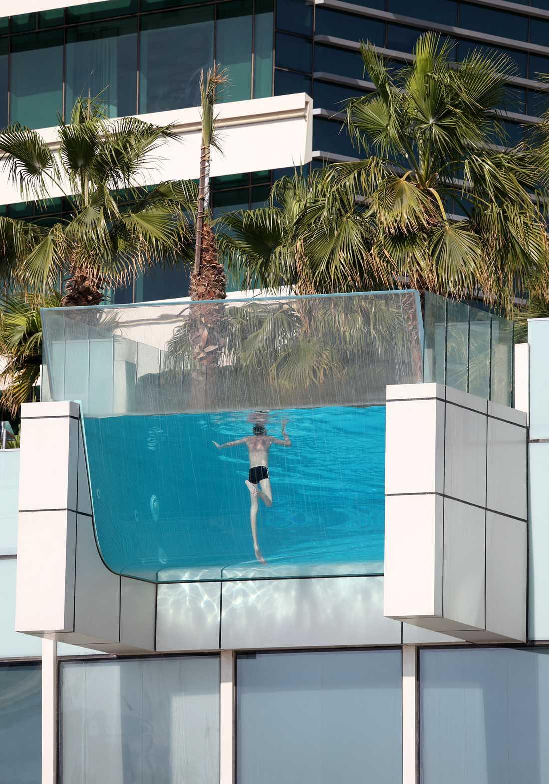 INTERCONTINENTAL HOTEL, DUBAI, FÖRENADE ARABEMIRATEN Poolen på hotellet i Festival City här botten och vägg helt i glas och sticker ut från fasaden, högt över marken. Du simmar med utsikt över bland annat Burj Khalifa, världens högsta byggnad. Invid poolen ligger en bar.