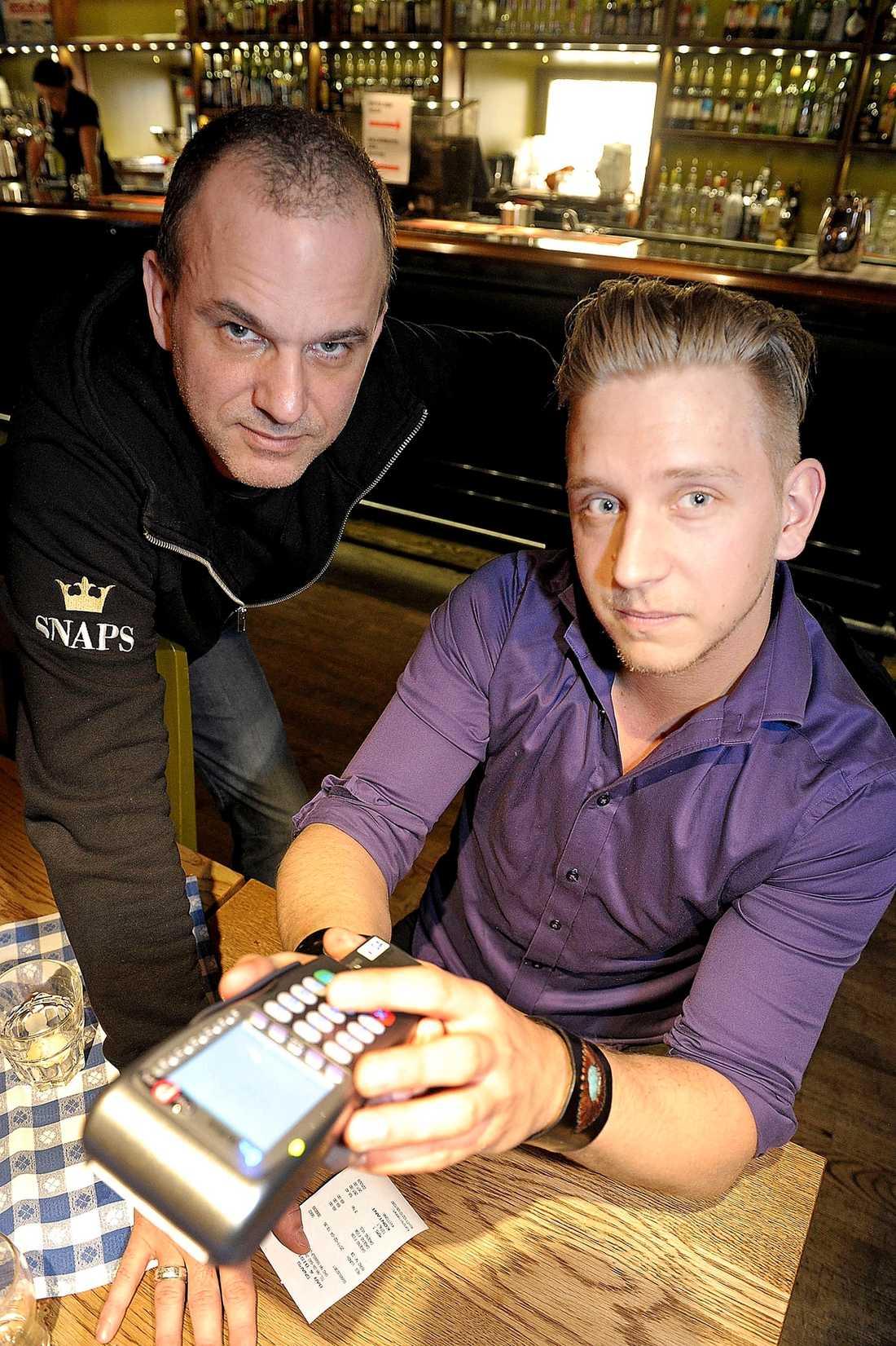 """kortslutning Pascal Lund tar betalt av Christian Nielsen på restaurang Snaps i Stockholm. """"Jag är stammis här så jag kan langa in kortet i baren på kvällarna. Annars är det kontanter som gäller. Betalar man med kort kan man få vänta hur länge som helst"""", säger Christian."""