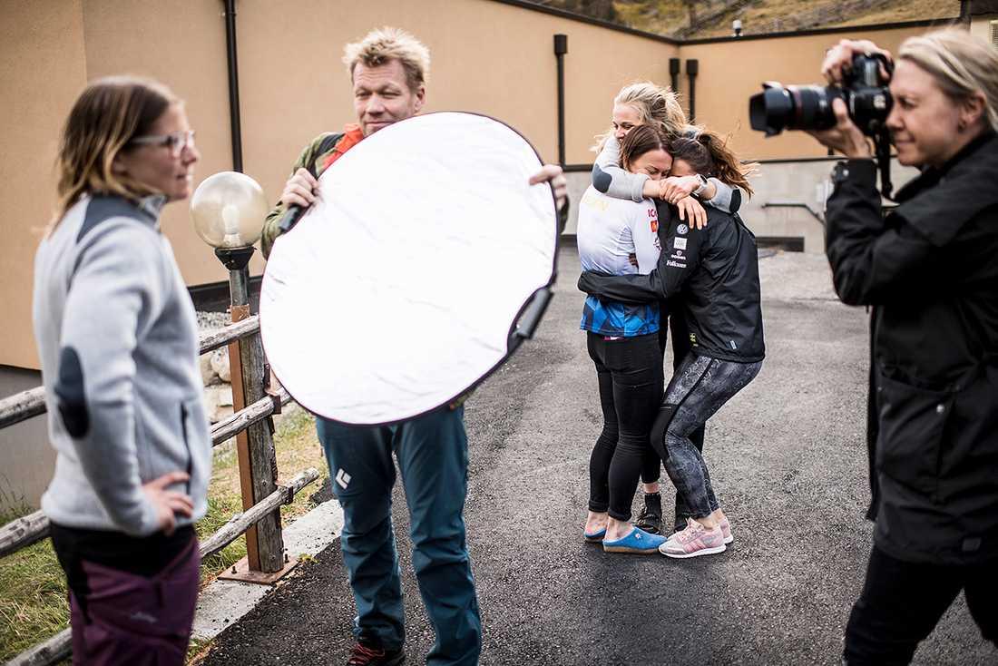 Stina Nilsson, Emma Wikén och Anna Haag värmer varandra med en gruppkram i den kalla alpluften.