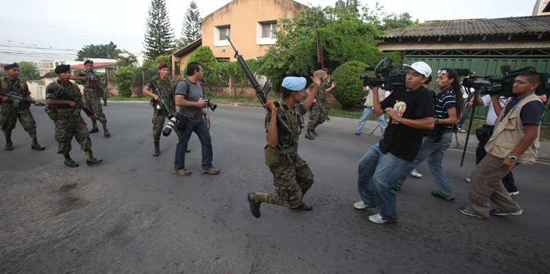 Soldater på patrull försöker få journalister att sluta filma utanför presidentpalatset i Tegucigalpa, Honduras. Det var på söndagen som militären stormade palatset, grep president och förde honom till en flygbas.