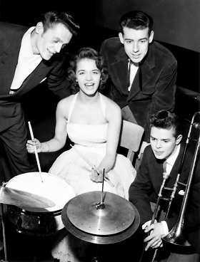 """1956 - skoljazztävling i Malmö. Lill-Babs omgiven av orkesterledarna Kjell """"Kolet"""" Hansson, Jan Poulsen och trombonisten och blivande jazz-stjärnan Eje Thelin (1938-1990)."""