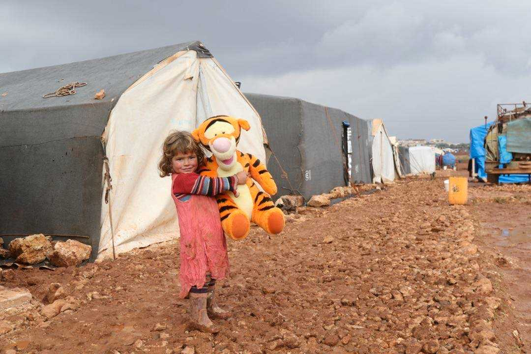 Khulod Khaled, 4 år, är föräldralös. Båda hennes föräldrar har dödats i kriget i Syrien. Genom Stand with Syria har hon fått ett eget gosedjur att bo med i det provisoriska flyktinglägret.