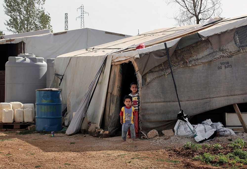 Syrianska barn på flykt står utanför sitt flyktingtält i det Syriska flyktinglägret i staden Majdal Anjar i Libanon. Inte sedan andra världskriget har lika många människor varit på flykt i världen –över 50 miljoner människor.