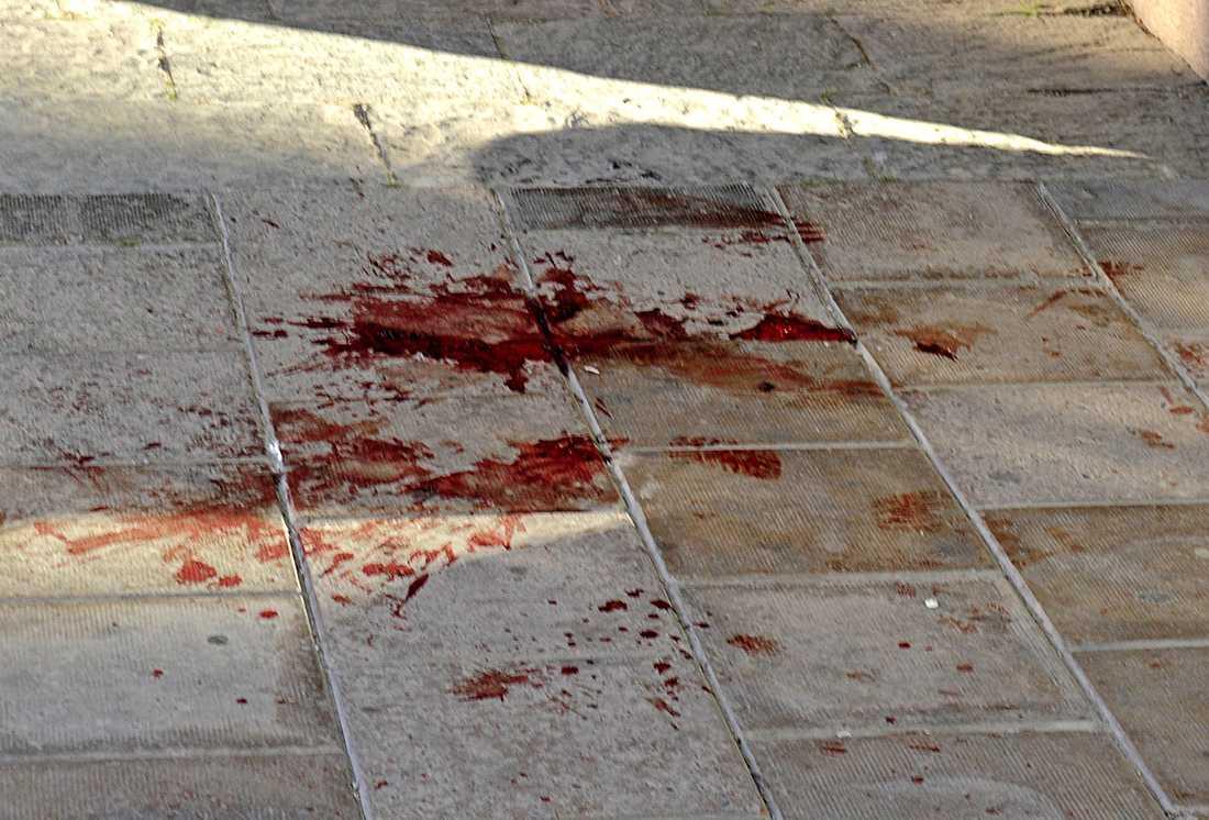 Blodfläck på marken efter knivdramat.