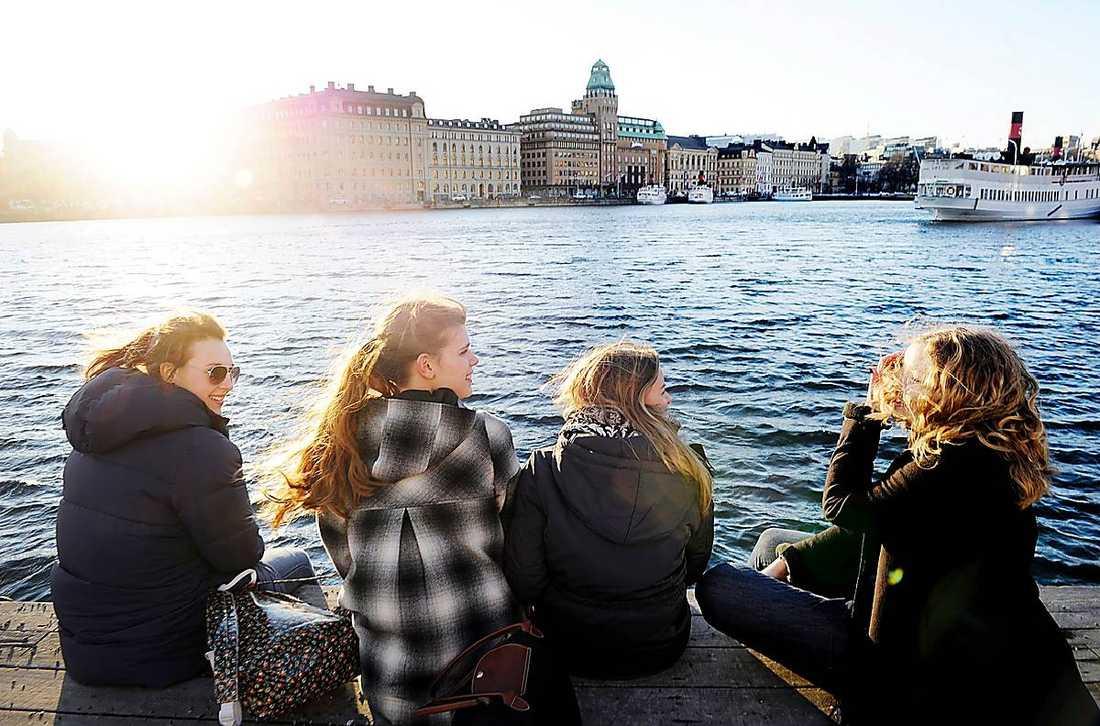 Solnjutare Katarina Andersson, Frida Svensson, Hanna Söderberg och Anna Avenberg njuter av vårsolen i centrala Stockholm.