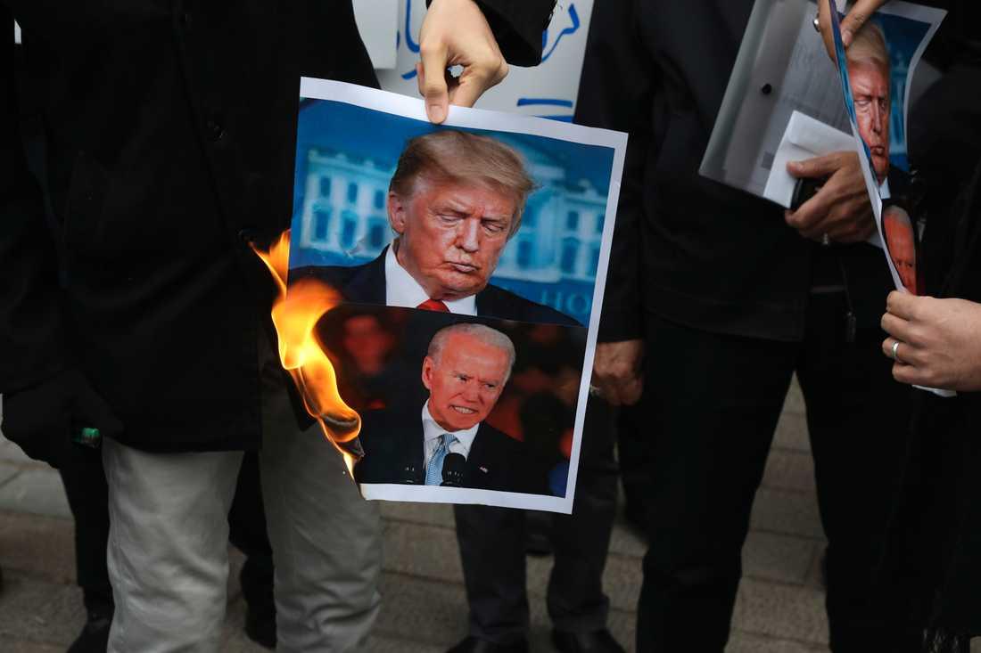 Demonstranter i Iran bränner en bild på USA:s nuvarande president Donald Trump och den tillträdande presidenten Joe Biden efter mordet på Mohsen Fakhrizadeh i Iran. USA:s allierade Israel har av Iran pekats ut som skyldig till mordet.