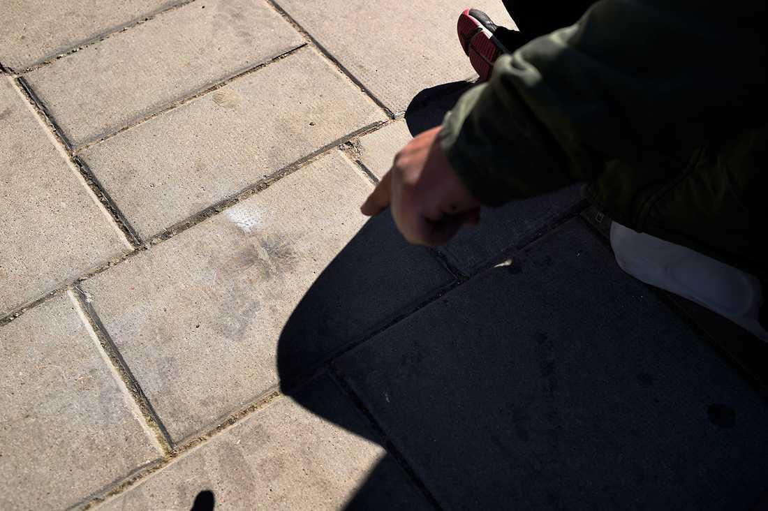 Calus visar märket efter knallskottet på trottoaren.