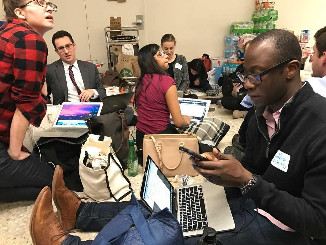 """Många advokater och andra jurister har tagit sig till Dulles-flygplatsen för att hjälpa till. I förgrunden sitter 35-årige Olivier Kamanda. """"Bland det viktigaste nu är att ta reda på vad vi behöver göra och vilka dokument som krävs för att se till att tullen följer det federala beslutet om att inga deportationer ska genomföras"""", säger han."""