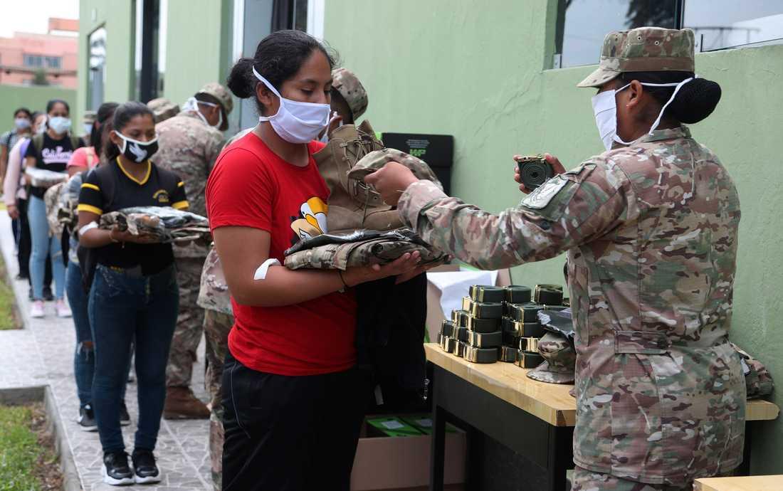 Soldater delar ut uniformer till reservister i Perus huvudstad Lima. Militärens och polisen kraftsamlar för att upprätthålla åtgärder som införts med anledning av coronaviruset.