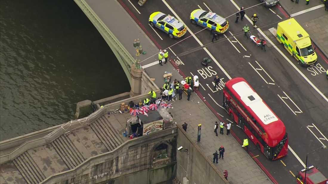Räddningspersonal tar hand om offren som mejades ner på Westminster bridge.