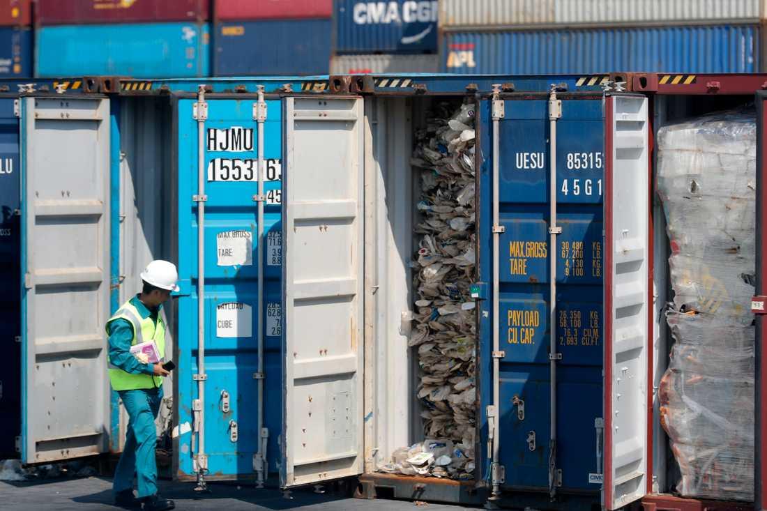En malaysisk tjänsteman inspekterar en container full av plastavfall. Arkivbild.