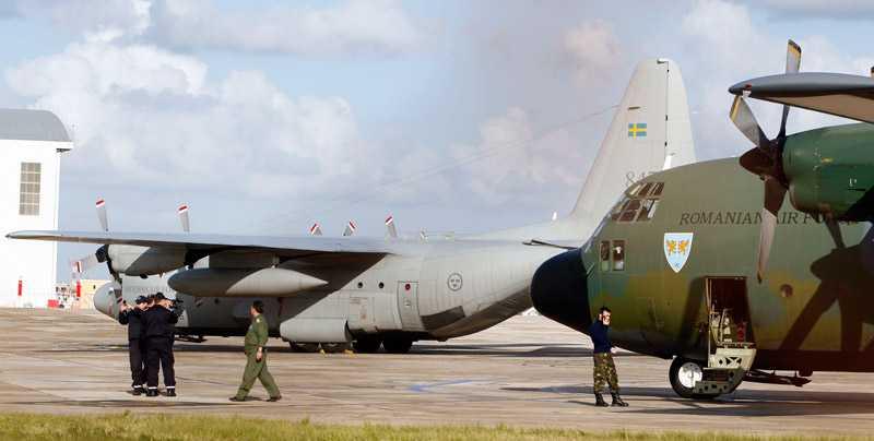 Det svenska Herculesplanet står standby på flygplatsen på Malta, redo att flyga hem svenskar från Libyen. I förgrunden ett rumänskt plan som lyckades flyga hem 50 personer från Tripoli på måndagen.