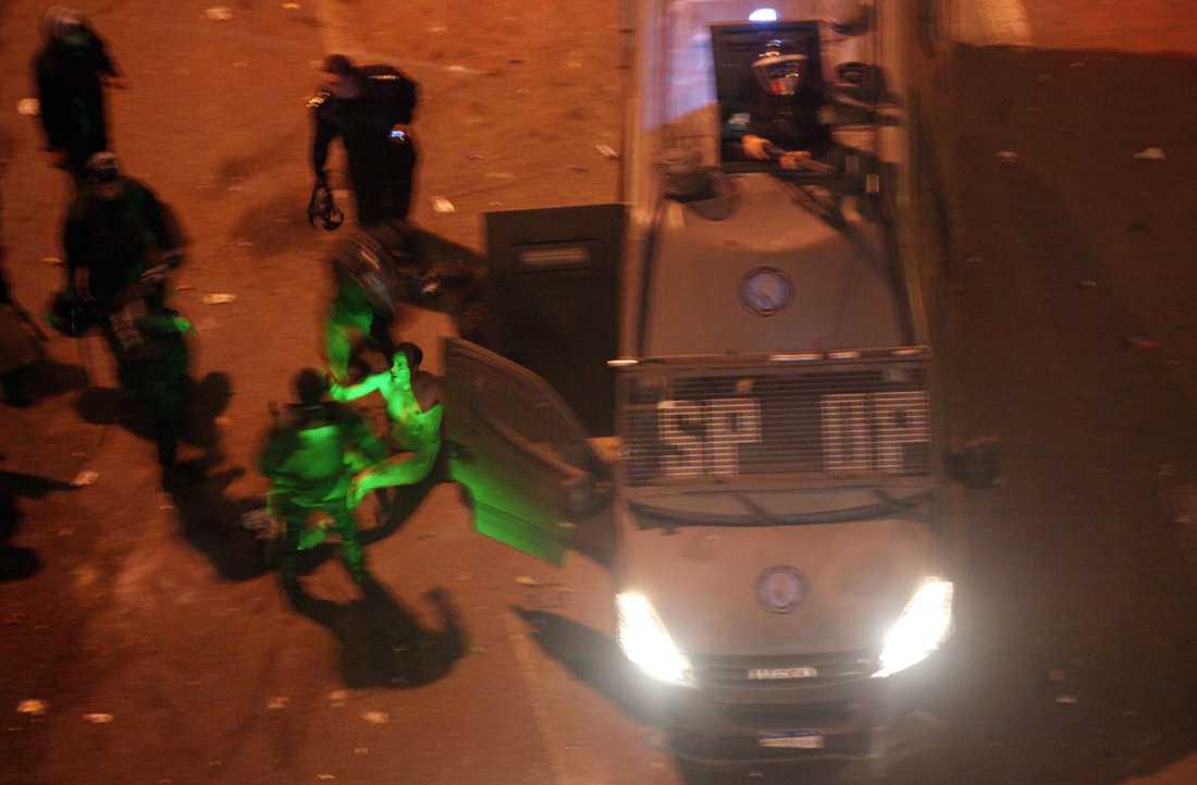 Laserljus lyser upp mannen när han dras in i en polisbuss.