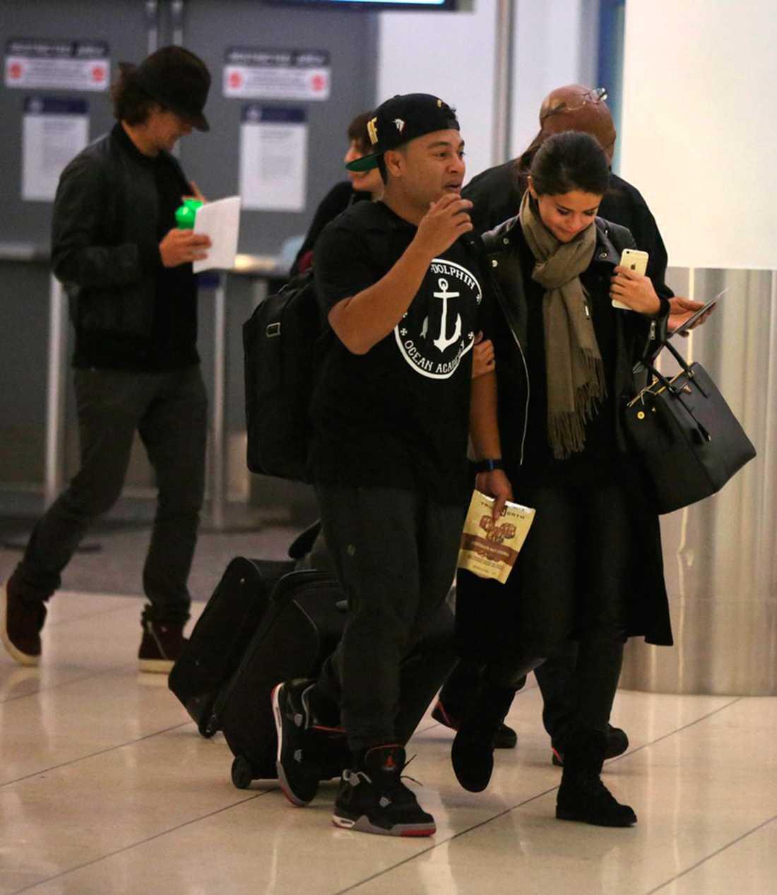 BILDBEVISET: Tittut! Orlando smyger bakom Selena på flygplatsen i Los Angeles.
