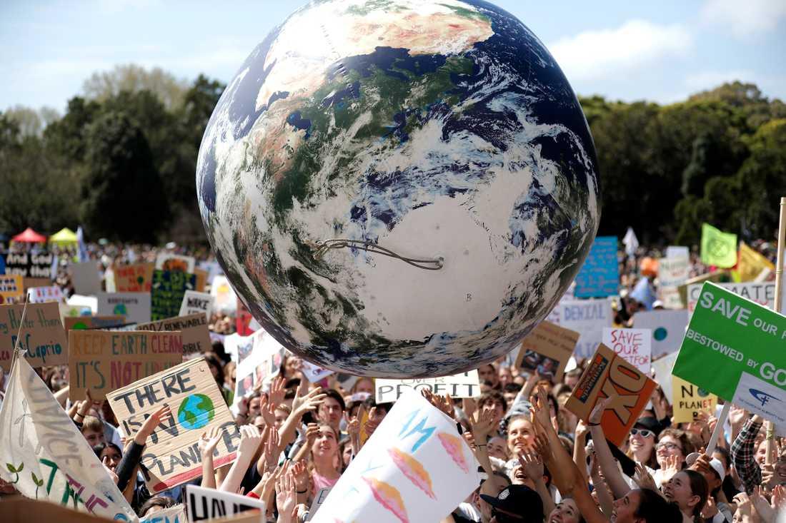 En stor uppblåsbar jordglob studsar över folkmassan i Sydney i Australien, där tusentals demonstranter samlats för klimatet.
