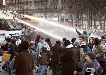 Ungdomsgängen anfaller med stenkastning. Polisen svarar med vattenkanoner och batonger.