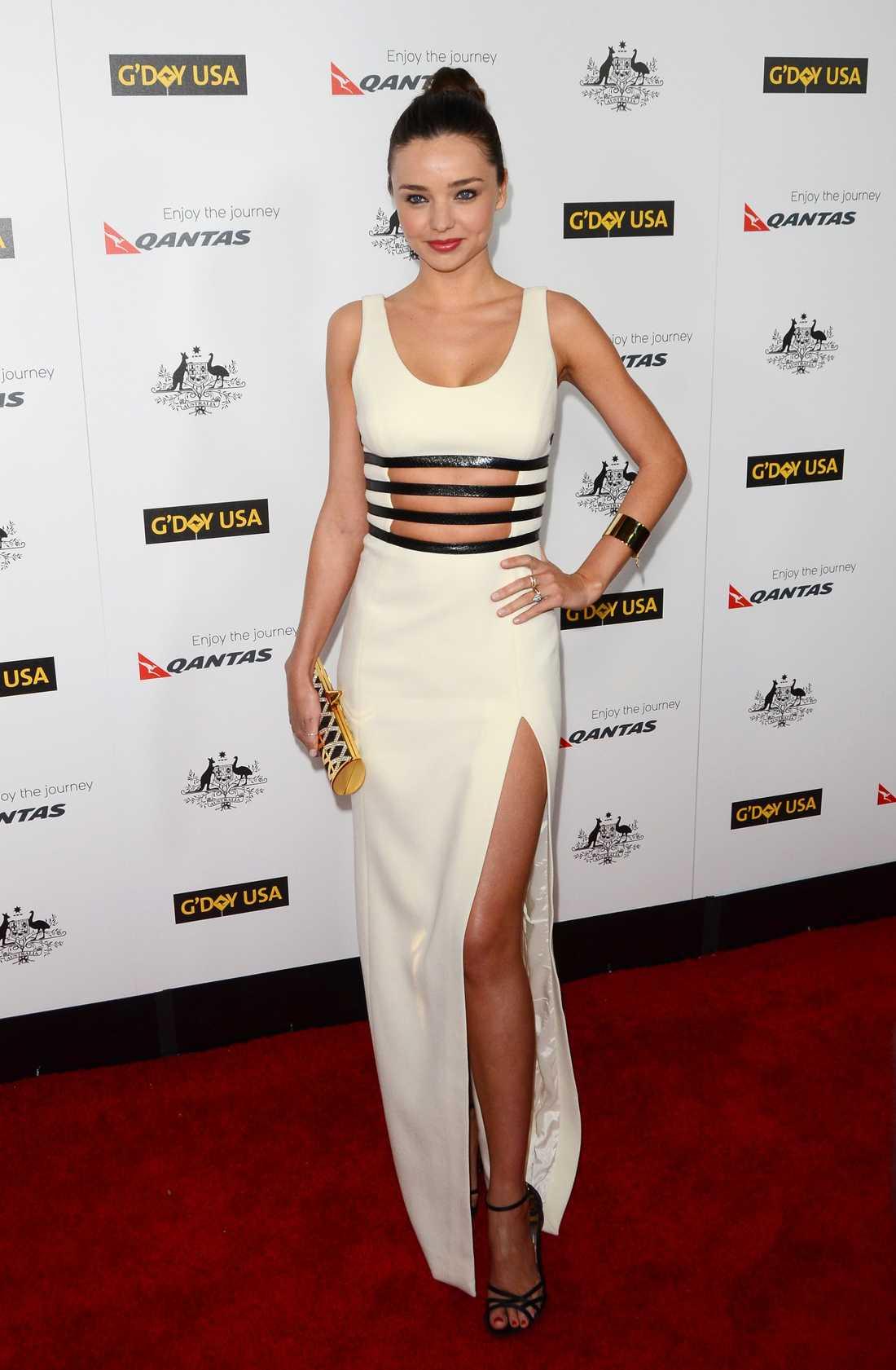 Miranda Kerr visade magen i denna vita Michael Kors-klänning med svarta detaljer. Med lårhög slits och i Dolce & Gabbana-klackar visade modellen även upp sina långa ben.