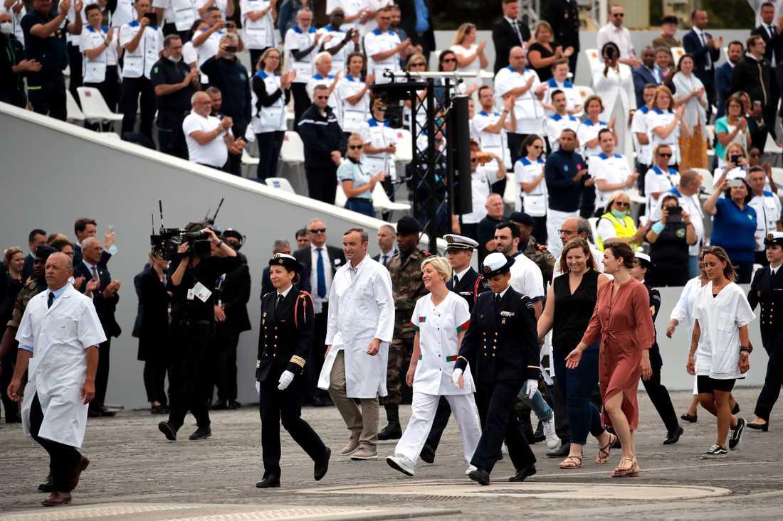 Vårdanställda och andra som gjort viktiga insatser under coronapandemin hyllas under nationaldagsfirandet i Paris.