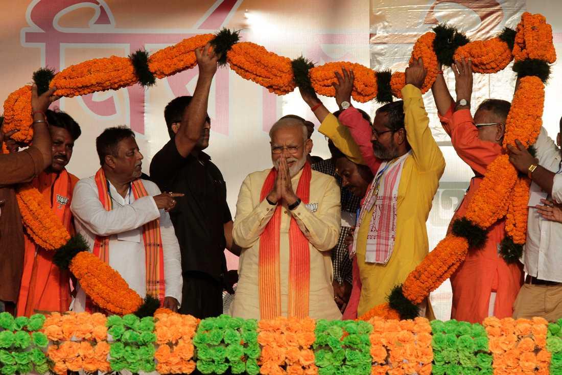 Indiens premiärminister Narendra Modi föräras med en enorm blomstergirlang vid ett valframträdande i Mathurapur i delstaten Västbengalen.
