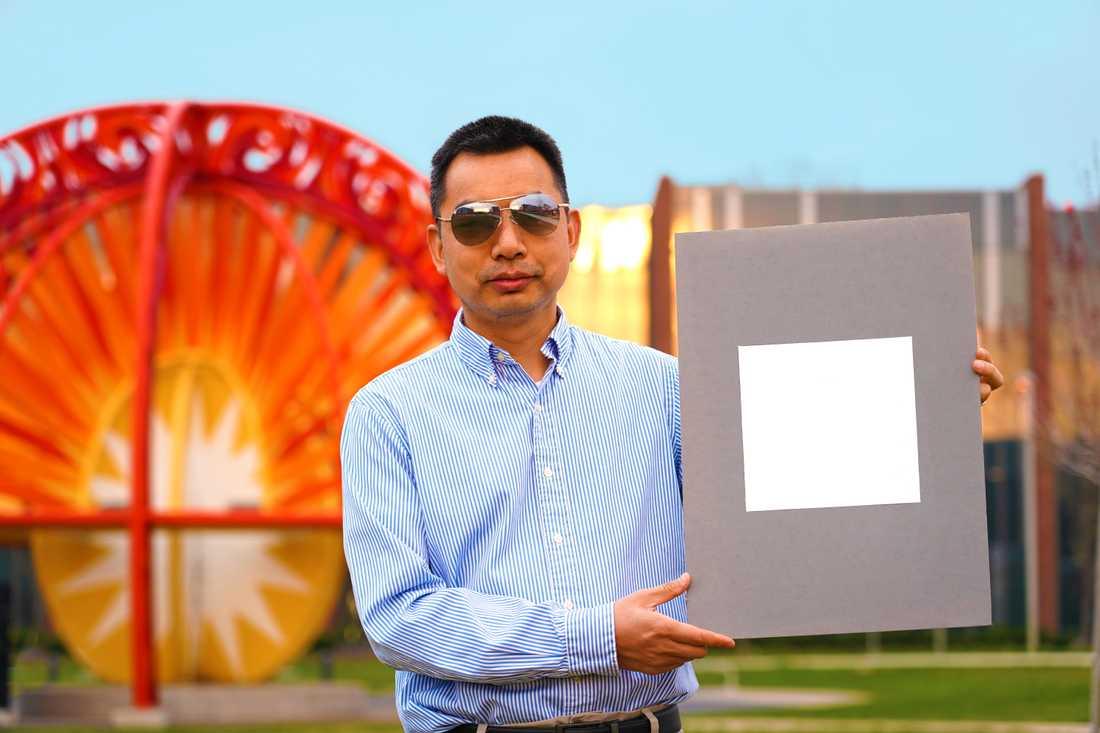 Professor Xiulin Ruan vid Purdue University i USA håller upp ett färgprov på den vitaste färgen som skapats.