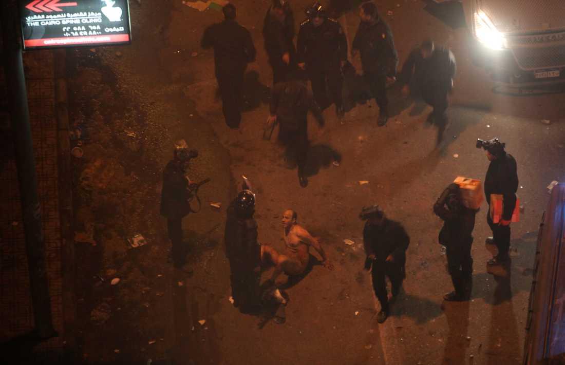 Kravallpolis misshandlar en av demonstranterna efter att först ha slitit av honom hans kläder.