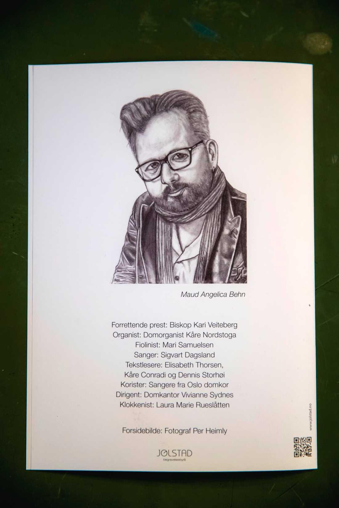Maud Angelica ställer ett inramat tecknat porträtt av sin pappa på kistan – samma porträtt som pryder programbladet.
