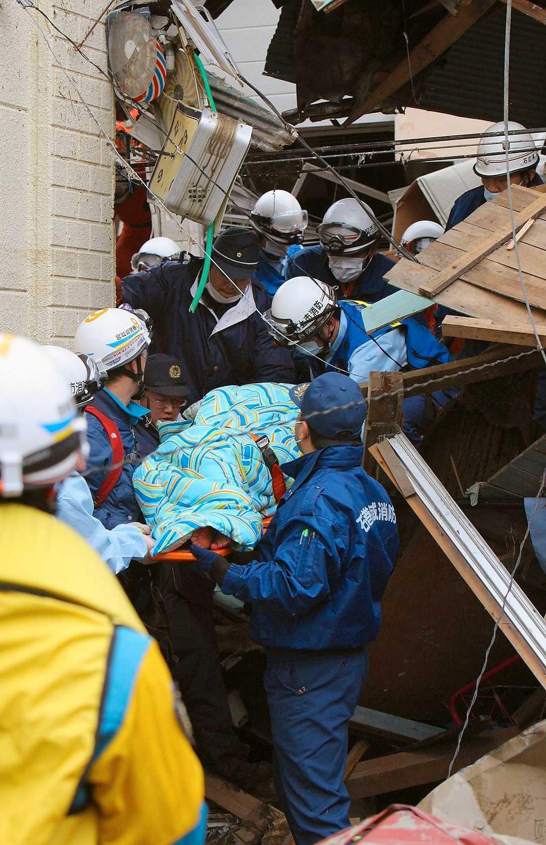 Räddningsarbetare bär ut Sumi Abe, 80, från det raserade huset i Ishinomaki.
