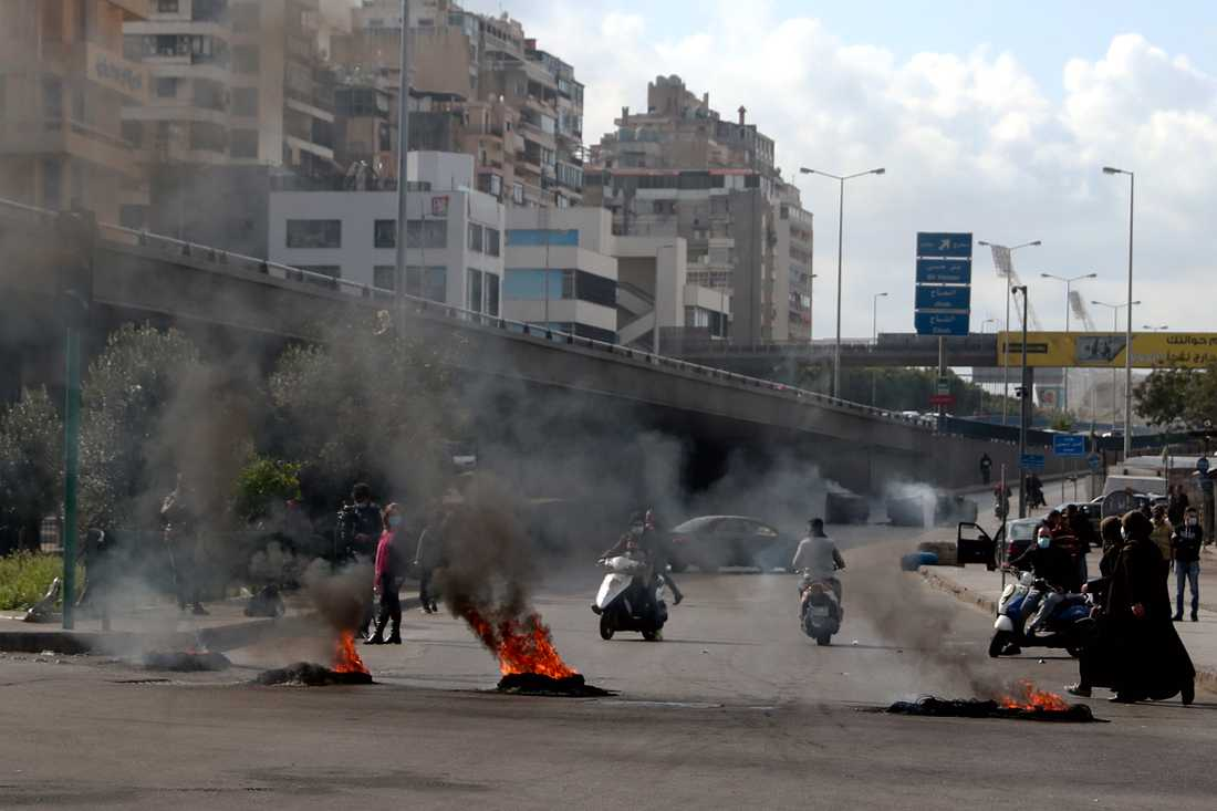Demonstranter bränner däck för att blockera en väg i Beirut i Libanon.