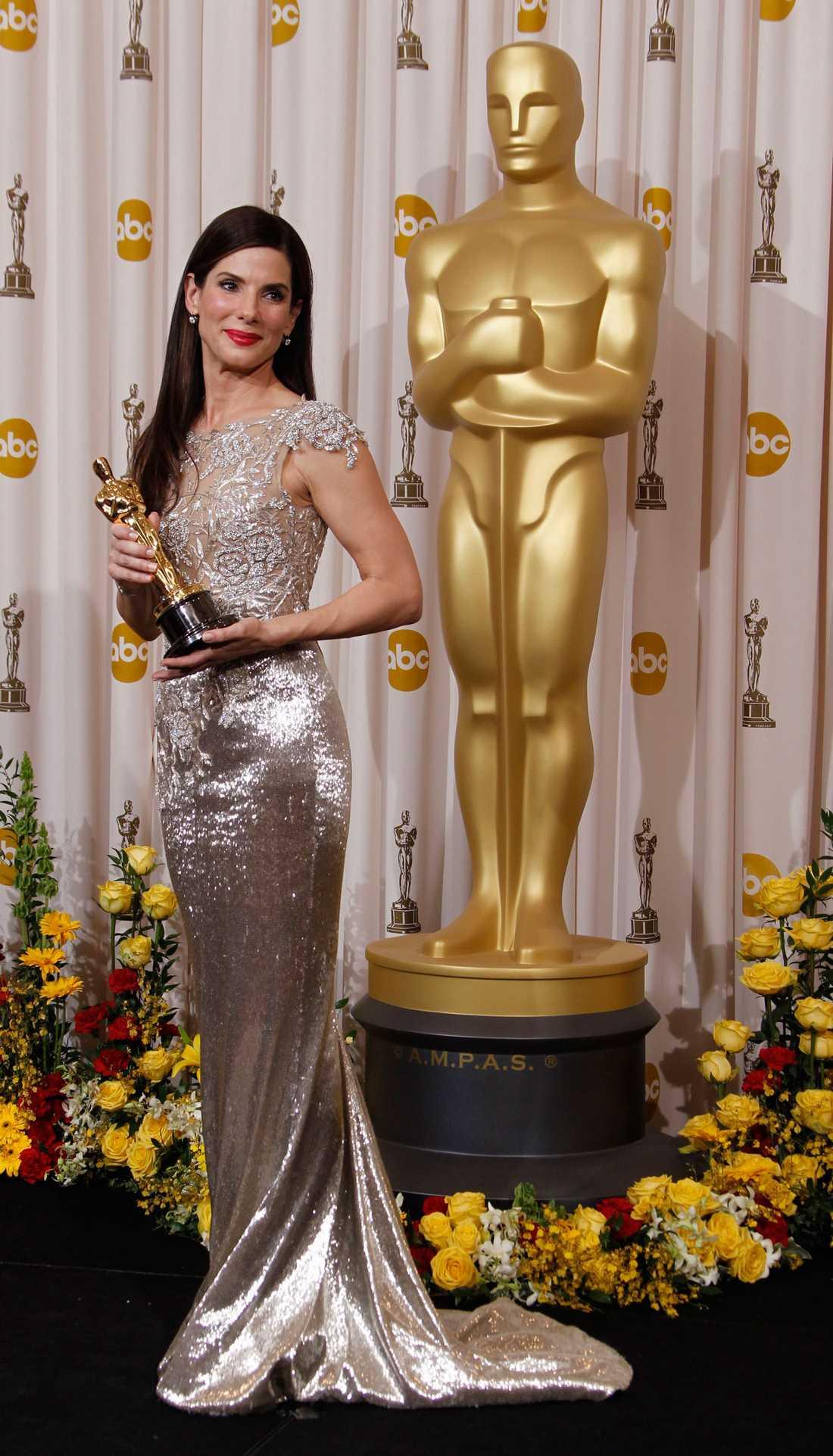 """Sandra Bullock 2010 """"Ibland blir en klänning så rätt att det nästan blir komiskt. De här guldiga kreationen från Marchesa gjorde att Bullock såg ut som en tvilling till statyetten i sin hand. Hon liksom smälte samman med Oscarsgubben och det kändes som att hon visste att hon skulle vinna med denna lycko-guld-klänning!"""""""